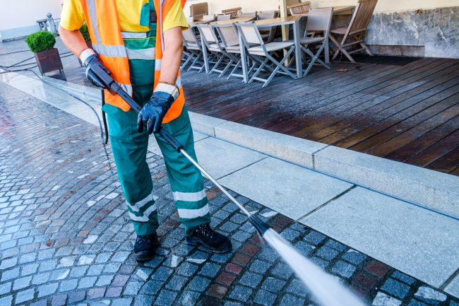 Worker cleaning the cobbled street in Ljubljana, Slovenia.