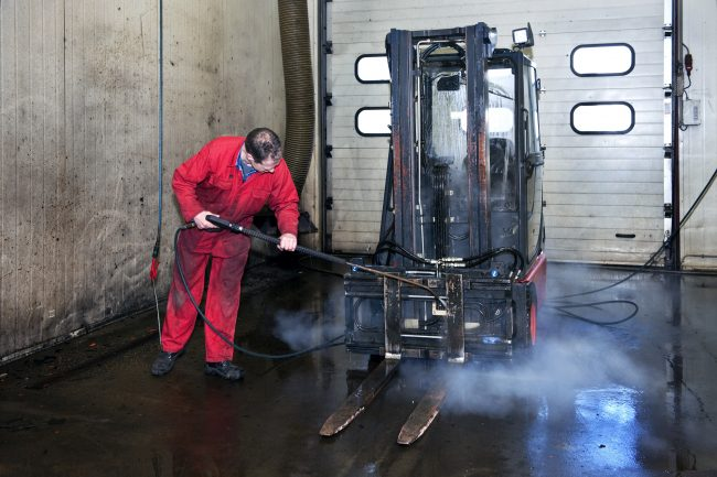 Man cleaning a forklift using a high pressure spray gun with hot, steaming, water